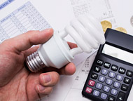 Person holding LED light bulb with calculator